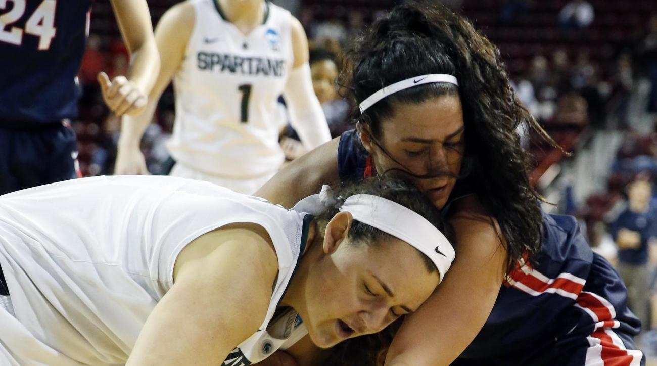 Michigan State center Jasmine Hines, left, and guard Branndais Agee, lower right, reach for a loose ball, knocked away from Belmont forward Frankie Joubran, center, during the first half in a first-round women's college basketball game in the NCAA Tournam