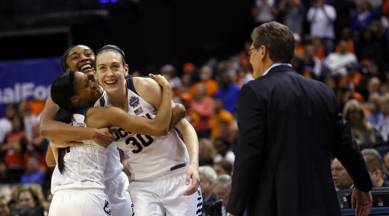 Connecticut's Morgan Tuck, left rear, Moriah Jefferson (4), and Breanna Stewart (30) hug as Connecticut head coach Geno Auriemma watches following the championship game against Syracuse in the women's Final Four in the NCAA college basketball tournament T