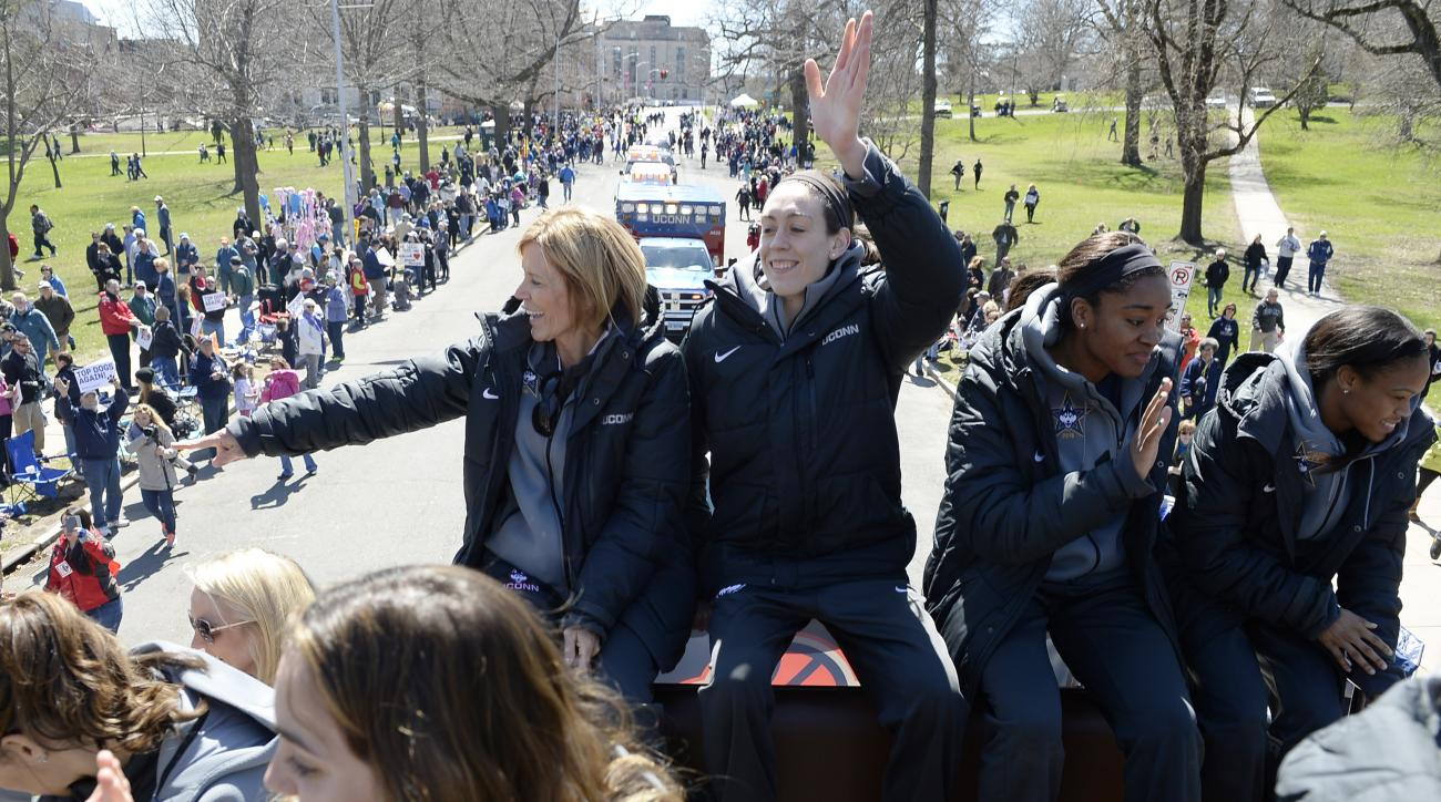 Connecticut associate head coach Chris Dailey, left, and players Breanna Stewart, center, Morgan Tuck, second from right, and Moriah Jefferson, right, wave to fans during a parade celebrating the team's unprecedented fourth consecutive NCAA college basket