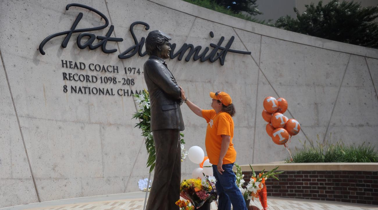 FILE - In this June 28, 2016, file photo, Teresa Olive, of Knoxville, Tenn., touches a statue of Pat Summitt as she pays her respects at the University of Tennessee in Knoxville, Tenn. Summitt vowed to make a difference in the fight against Alzheimer's di