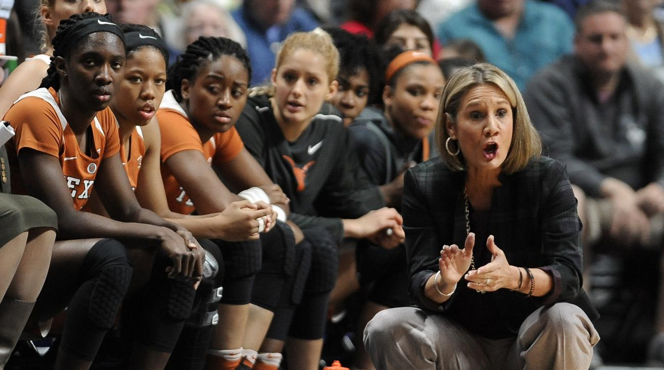 FILE - In this Sunday, Dec. 4, 2016, Texas head coach Karen Aston, right, urges on her players in the first half of an NCAA college basketball game in Uncasville, Conn. Texas (2-4) will remain below .500 whether it wins or loses Sundays matchup against Te