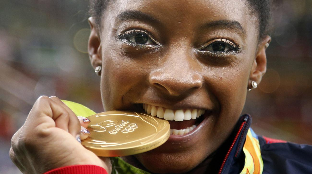 FILE - In this Aug. 11,2 016 file photo, United States' Simone Biles bites her gold medal for the artistic gymnastics women's individual all-around final at the 2016 Summer Olympics in Rio de Janeiro, Brazil. Briles was selected as the AP Female Athlete o
