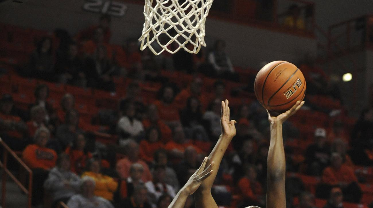 Baylor guard Kalani Brown (21) watches as Oklahoma State guard Diana Omozee (5) takes a shot over the defense of Baylor forward Dekeiya Cohen (1) during an NCAA college basketball game in Stillwater, Okla., Satruday, Jan. 7, 2017. (AP Photo/Brody Schmidt)