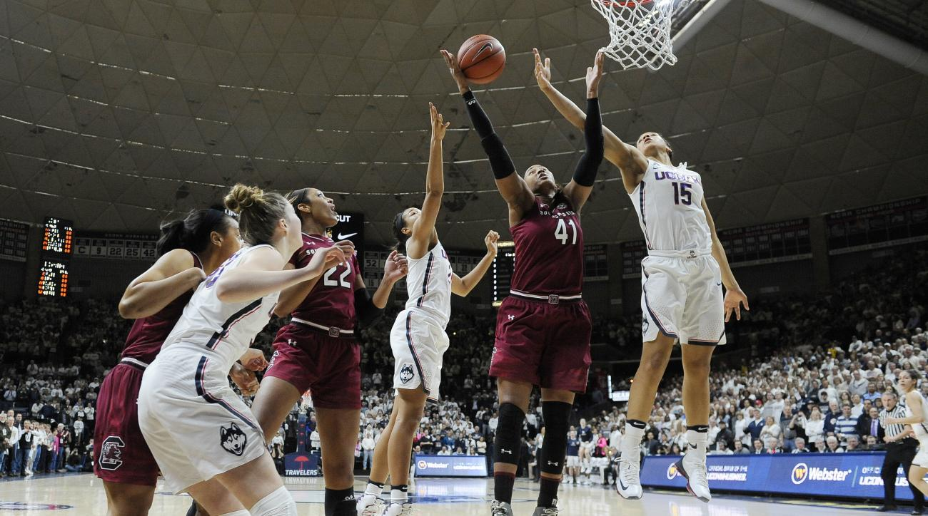 South Carolina's Alaina Coates, center, pulls down a rebound between Connecticut's Napheesa Collier and Connecticut's Gabby Williams, right, in the first half of an NCAA college basketball game, Monday, Feb. 13, 2017, in Storrs, Conn. (AP Photo/Jessica Hi