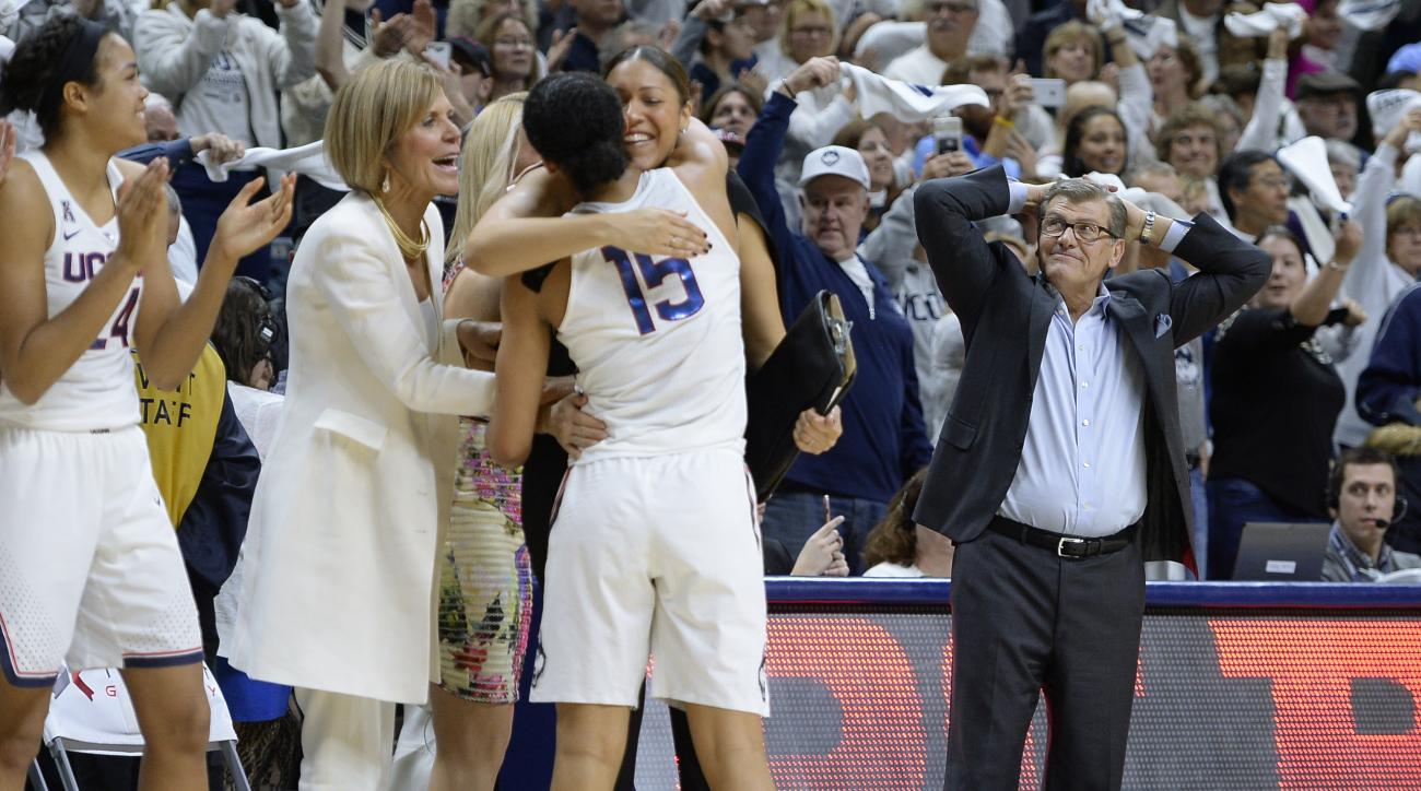 Connecticut head coach Geno Auriemma, right, reacts as Connecticut's Gabby Williams (15) is congratulated by associated head coach Chris Dailey and embraced by assistant coach Marisa Moseley at the end of an NCAA college basketball game against South Caro