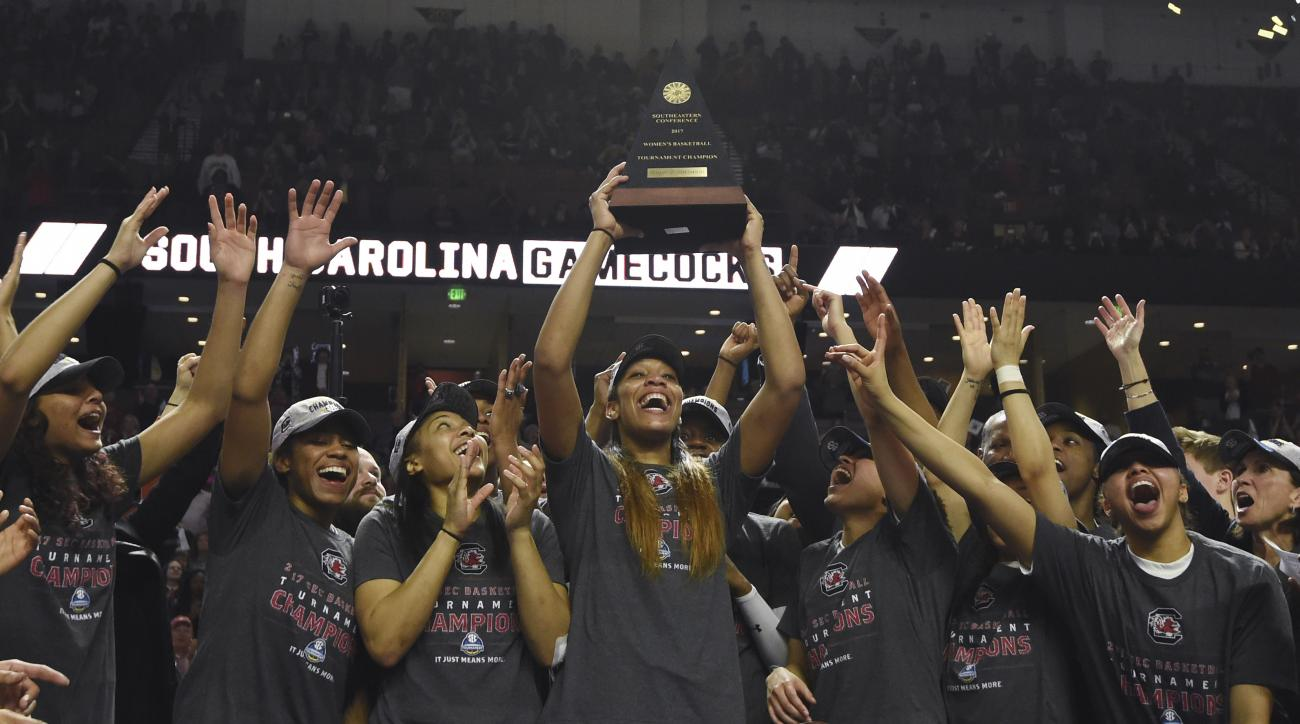 South Carolina forward A'ja Wilson (22) holds the trophy as she celebrates with teammates after defeating Mississippi State in an NCAA college basketball game during the Southeastern Conference tournament on Sunday, March 5, 2017, in Greenville, S.C. Wils