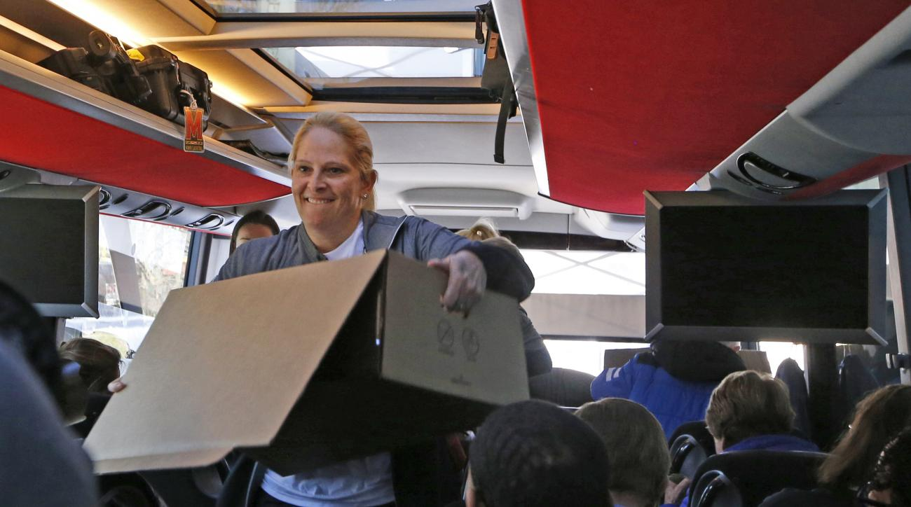 Maryland coach Brenda Frese squeezes through a narrow aisle with a box of food in the team's cramped bus, Thursday, March 23, 2017, after the team arrived in Stamford, Conn., for this weekend's Bridgeport Regional in the NCAA women's college basketball to