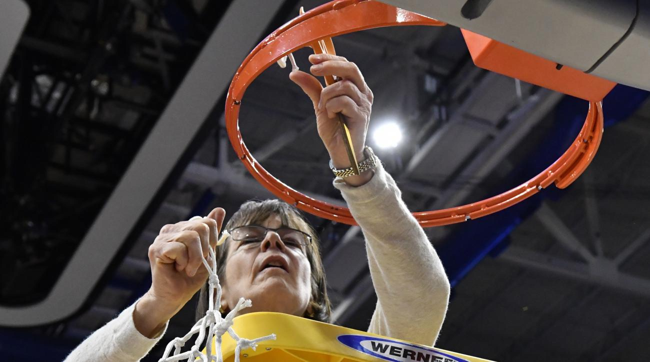 Stanford's head coach Tara VanDerveer pulls down the final bit of the net after her team defeated Notre Dame 76-75 to win the Lexington regional final of the NCAA women's college basketball tournament, Sunday, March. 26, 2017, in Lexington, Ky. (AP Photo/