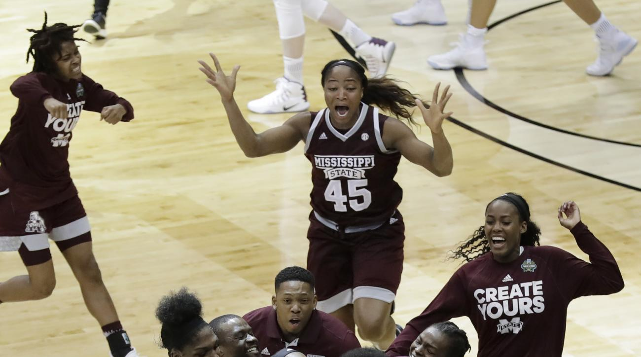 Mississippi State guard Morgan William, center, celebrates with teammates after she hit the winning shot at the buzzer in overtime to defeat Connecticut in an NCAA college basketball game in the semifinals of the women's Final Four, Friday, March 31, 2017