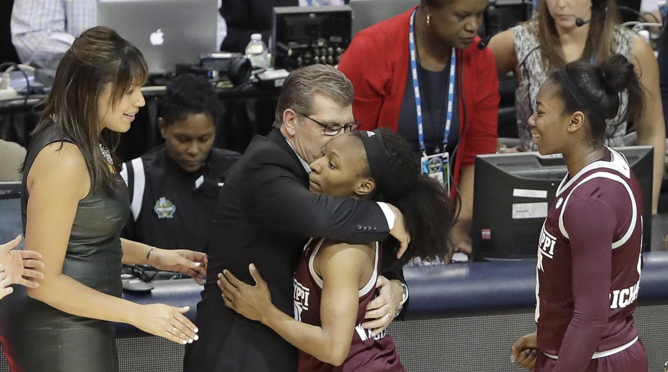 Mississippi State guard Morgan William (2) is hugged by Connecticut head coach Geno Auriemma, center, after their NCAA college basketball game in the semifinals of the women's Final Four, Friday, March 31, 2017, in Dallas. Mississippi State won 66-64. (AP