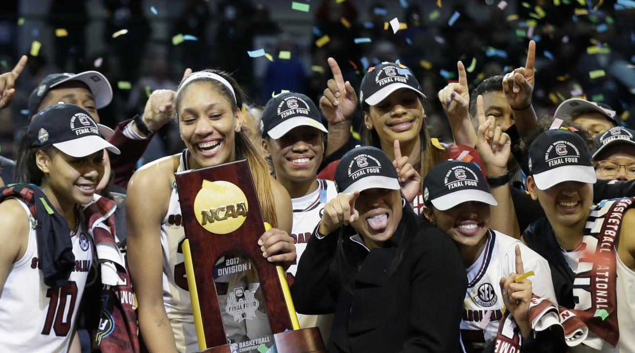 South Carolina forward A'ja Wilson holds the trophy and coach Dawn Staley points as the team celebrates a win over Mississippi State in the final of NCAA women's Final Four college basketball tournament, Sunday, April 2, 2017, in Dallas. South Carolina wo