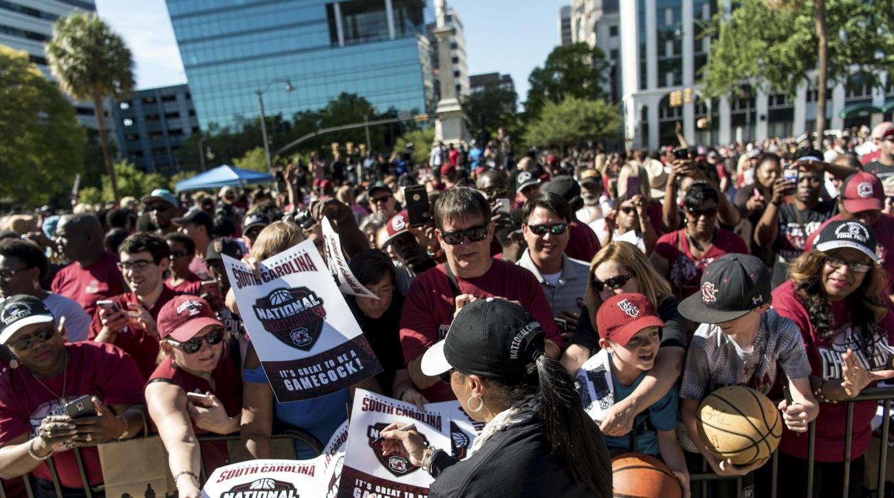 FILE- In this April 9, 2017, file photo, South Carolina head coach Dawn Staley signs autographs for fans at the conclusion of the South Carolina women's basketball National Championship parade in Columbia, S.C. South Carolina leaves June 27 and will play